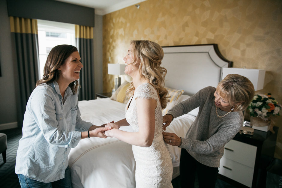 katie putting on her bridal gown with mom and sister